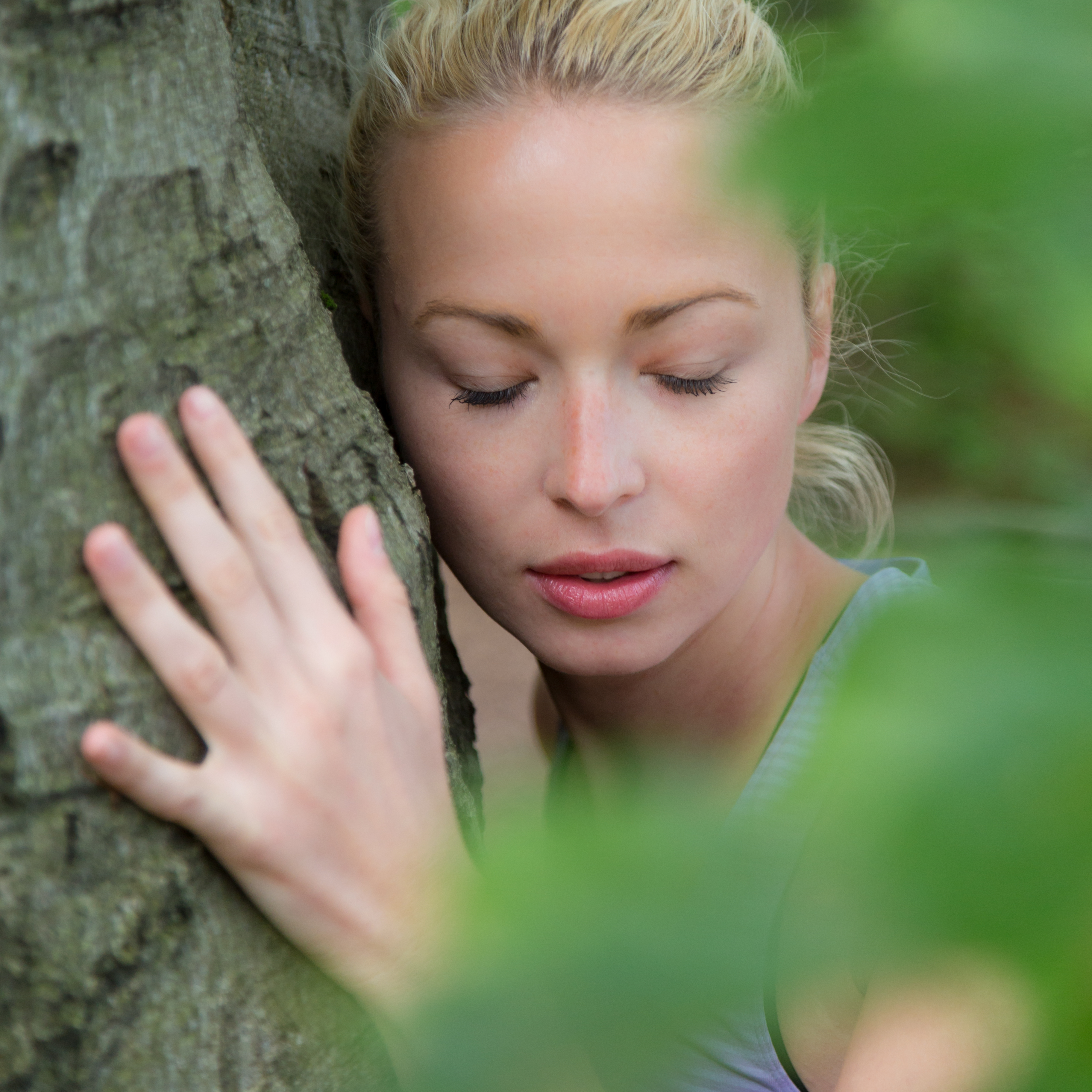 Woman listening with her ear agains a tree